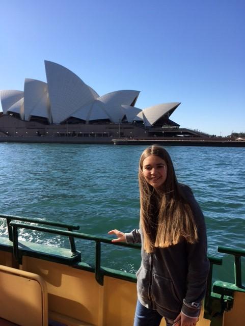 Niña en un ferry frente a Opera House de Sidney en Australia