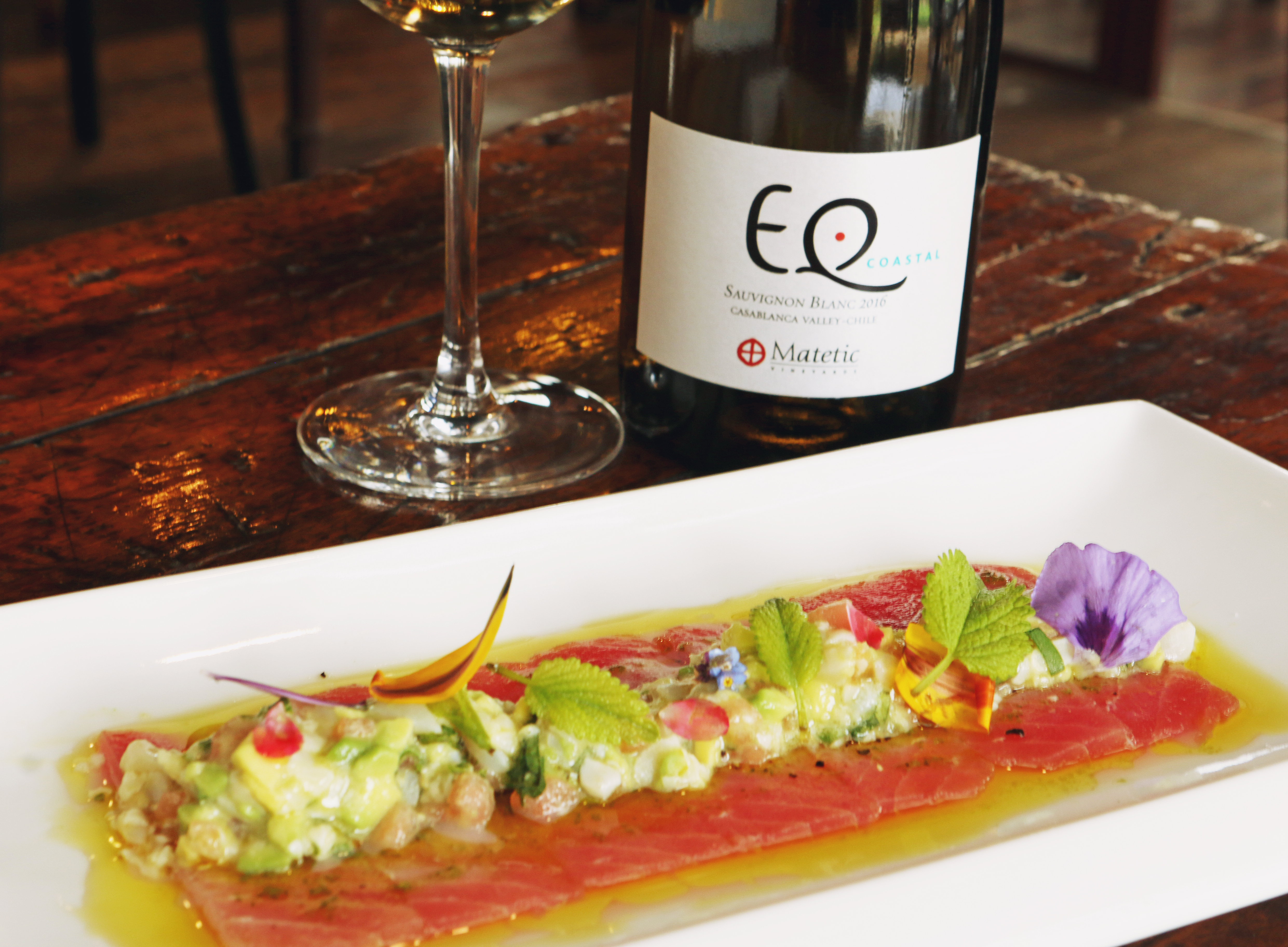 Plato y copa de vino en Restaurante Equilibrio en Viña Matetic