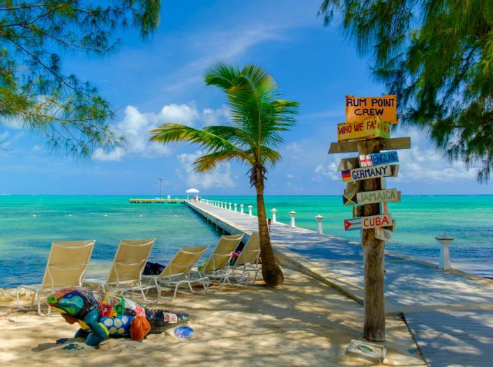 Playa Rum Point con reposeras y cartel de colores en Islas Caimán