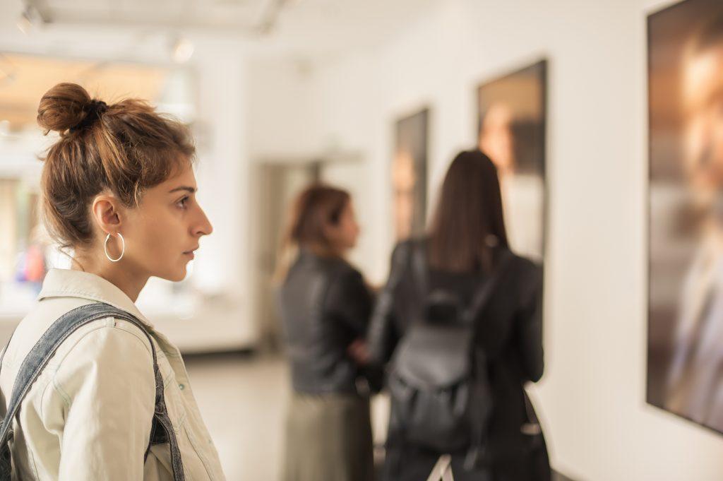Mujer mirando un cuadro en museo