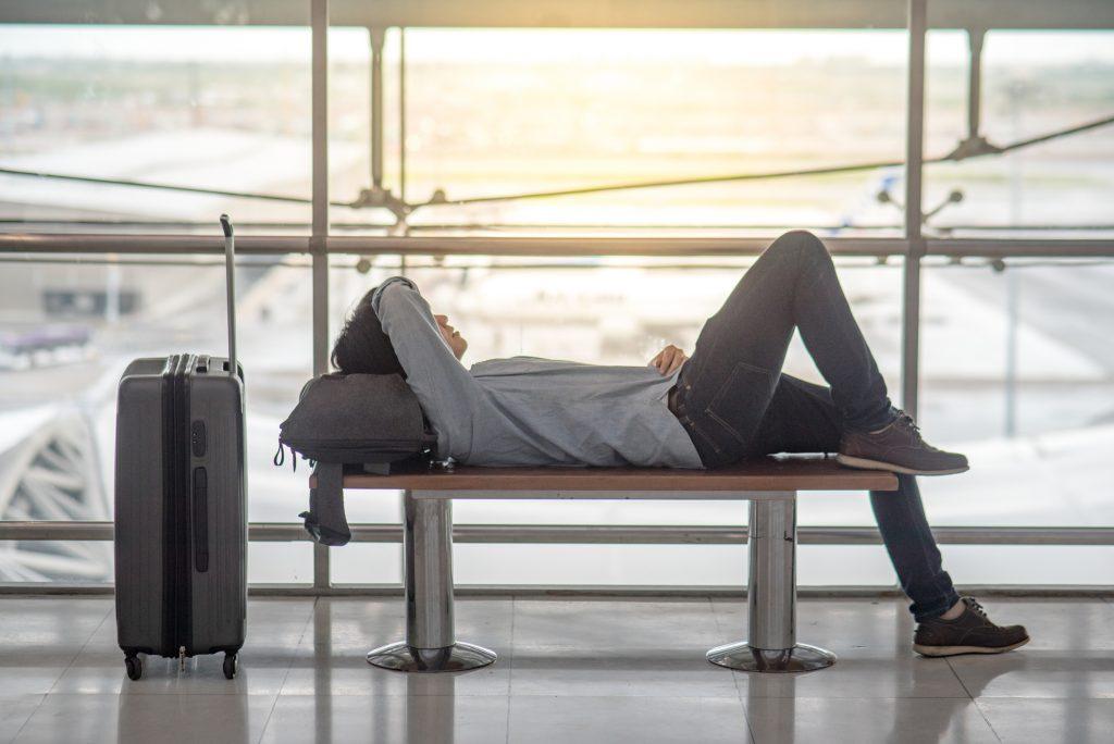 Hombre tapandose la cara acostado en el aeropuerto