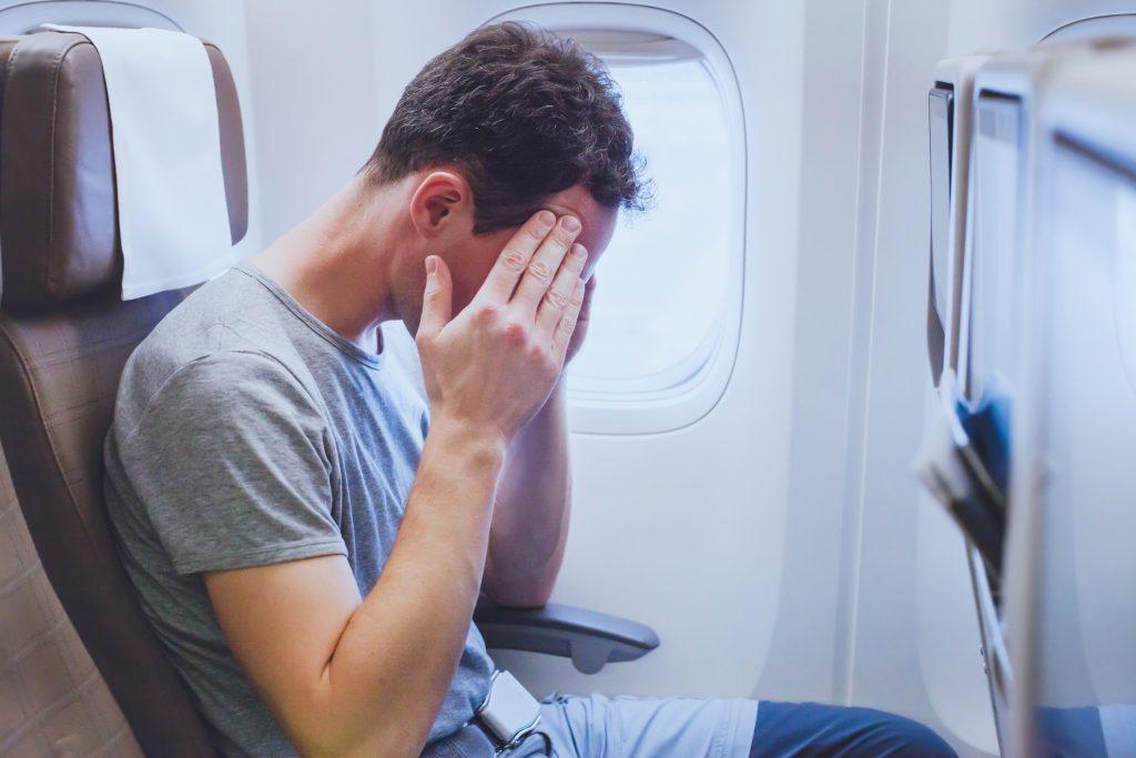 Hombre con dolor de cabeza en un avion